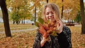 Uma moça que levanta alegremente na câmera com um ramalhete das folhas coloridas Ande no parque da cidade no outono filme