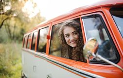 Uma moça que olha fora de um carro em um roadtrip através do campo imagem de stock