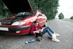 Uma moça que senta-se perto de um carro quebrado e que procura a ajuda, ao lado dela lá é peças más, o gerador bonde, ferramentas fotos de stock royalty free