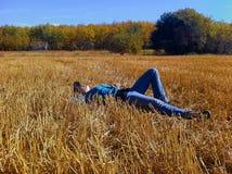 Uma moça que toma uma ruptura ao trabalhar em uma exploração agrícola, estabelecendo em um campo da palha que olha acima no céu fotografia de stock royalty free
