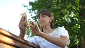 Uma moça que usa um smartphone está escrevendo uma letra em um banco em um parque verde bonito Mulher milenar nova no filme