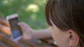 Uma moça que usa um smartphone está lançando através das páginas em uma loja em linha no parque em um banco Milenar novo vídeos de arquivo