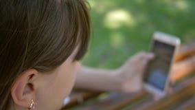 Uma moça que usa um smartphone está lançando através das páginas em uma loja em linha no parque em um banco Milenar novo video estoque