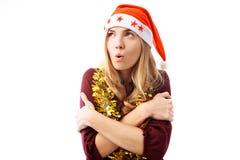 Uma moça que veste um chapéu de Santa está fria e está aquecendo-se, imagens de stock royalty free