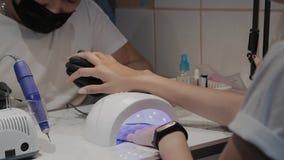Uma moça seca o verniz para as unhas sob uma lâmpada ultravioleta no salão de beleza do tratamento de mãos vídeos de arquivo