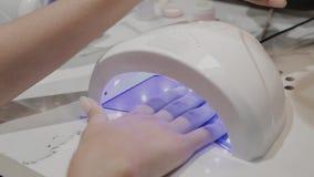 Uma moça seca o verniz para as unhas sob uma lâmpada ultravioleta no salão de beleza do tratamento de mãos filme