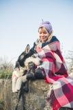 Uma moça senta com seu amigo o cão ronco na borda do desfiladeiro no por do sol Foto de Stock