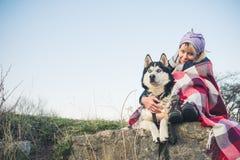 Uma moça senta com seu amigo o cão ronco na borda do desfiladeiro no por do sol Foto de Stock Royalty Free