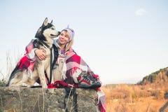 Uma moça senta com seu amigo o cão ronco na borda do desfiladeiro no por do sol Imagens de Stock