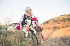 Uma moça senta com seu amigo o cão ronco na borda do desfiladeiro no por do sol Fotos de Stock