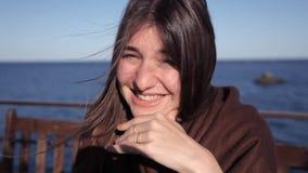 Uma moça senta-se em um café pelo mar e pelos risos Um forte vento funde em seu cabelo vídeos de arquivo