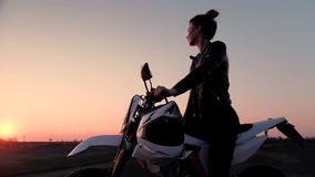 Uma moça senta-se montado em uma motocicleta e olha-se o por do sol bonito filme