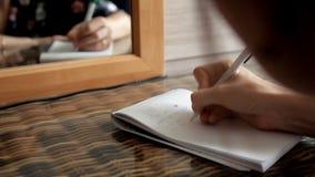 Uma moça senta-se na frente de um espelho toma notas em um caderno eu te amo e em números video estoque