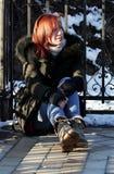 Uma moça senta-se no assoalho, nos braços em torno de seus joelhos, nos sorrisos e nos olhares afastado em um dia de inverno enso fotos de stock royalty free