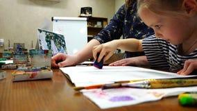 Uma moça sob o controle do ` s do professor umedece o papel com água vídeos de arquivo