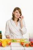 Uma moça tenta cortar o aipo desbastado vegetariano para a salada vegetal Foto de Stock Royalty Free