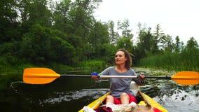 Uma moça trabalha duramente com uma pá em um caiaque no rio video estoque