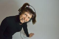 Uma moça, uma mulher com fones de ouvido e um microp Foto de Stock Royalty Free