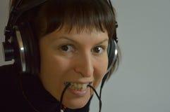 Uma moça, uma mulher com fones de ouvido e um microp Imagens de Stock