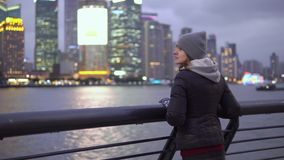 Uma mo?a em um revestimento e em um chap?u pretos olha as vistas de Shanghai na margem do Vaitan filme