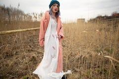Uma mo?a em um vestido branco bonito e em um chap?u ? moda levanta em um campo de trigo fotografia de stock royalty free