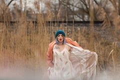 Uma mo?a em um vestido branco bonito e em um chap?u ? moda levanta em um campo de trigo imagens de stock royalty free
