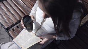 Uma mo?a no parque em um banco que l? um livro e que bebe o caf? de uma caneca A vista da parte superior vídeos de arquivo