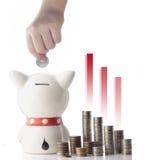 Uma moeda da economia da mão no banco piggy Fotos de Stock Royalty Free