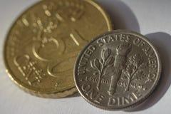 Uma moeda de dez centavos americana sobre o centavo de Euro 50 D Fotos de Stock