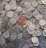Uma moeda do centavo em uma pilha de 10 moedas do centavo Fotos de Stock Royalty Free