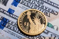Uma moeda do dólar - a estátua da liberdade - em cem dólares de contas Fotografia de Stock