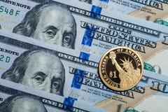 Uma moeda do dólar - a estátua da liberdade - em cem dólares de contas Imagens de Stock