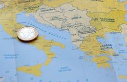 Uma moeda do Euro em um mapa europeu Fotografia de Stock Royalty Free