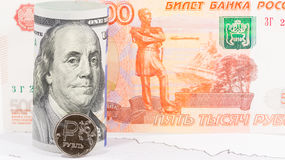 Uma moeda do rublo de russo contra 100 cédula do dólar americano Fotos de Stock Royalty Free
