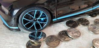 Uma moeda israelita do shekel perto do brinquedo do metal do preto de Bugatti Chiron com reflexão do dinheiro da roda imagens de stock
