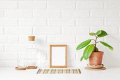Uma moldura para retrato de madeira vazia com espaço branco da cópia na tabela Imagem de Stock