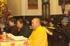 Uma monge budista com uma veste amarela está rezando no templo de Yuantong foto de stock