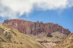 Uma montanha da pedra calcária vermelha no meio de outras amarelas fotos de stock royalty free