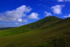 Uma montanha sob o céu azul nebuloso Foto de Stock Royalty Free