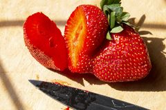 Uma morango do corte com uma faca foto de stock royalty free