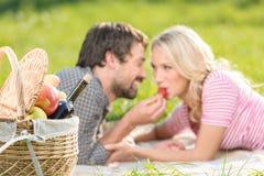 Uma morango para ela. Homens novos que alimentam sua amiga com stra Imagens de Stock Royalty Free