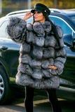 Uma morena bonita em um casaco de pele curto, em umas calças pretas e em um tampão preto está perto do carro em um dia ensolarado imagem de stock royalty free