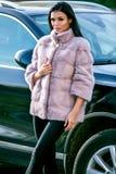 Uma morena bonita em um casaco de pele luz-colorido e em uma calças preta está estando perto de um carro em um dia ensolarado do  fotos de stock royalty free