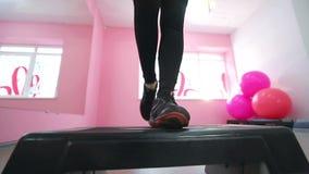 Uma morena bonito executa exercícios da aptidão da aptidão na frente de um espelho Emagrecimento no gym Estilo de vida saudável video estoque
