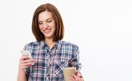 Uma morena de sorriso bonita nova com uma xícara de café ou um chá lê uma mensagem agradável em seu telefone celular Copie o espa fotografia de stock