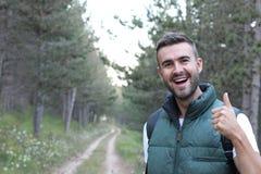 Uma morena de sorriso e de riso guardando os polegares acima na aprovação ao estar no meio de uma caminhada da floresta O grande  foto de stock royalty free