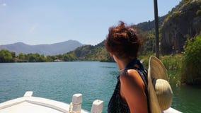 Uma morena em uma navigação do chapéu em um barco branco ao longo do rio de Dalyan e aprecia a paisagem da montanha Plano m?dio vídeos de arquivo