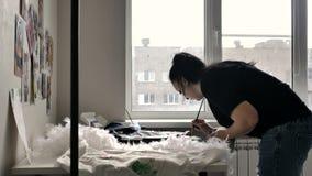 Uma morena em um t-shirt preto e em calças de brim tira vídeos de arquivo