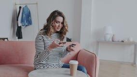 Uma morena encaracolado natural que faz um pagamento do cartão através do telefone celular às faturas pagamento Uma menina atr video estoque
