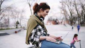 Uma morena na moda nova está sentando-se em um banco com um portátil em seus joelhos, datilografando Fones de ouvido no pescoço,  filme